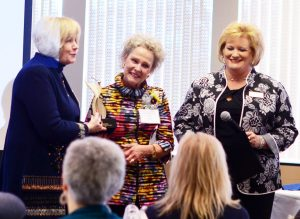 2017 Athena recipient Pam Hall receiving the Athena statue from program chair Diane Glassmeyer and WBC president Terri Martin.